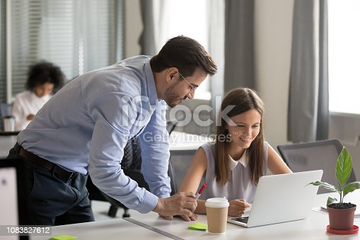 istock Friendly mentor explaining task young female employee 1083827612