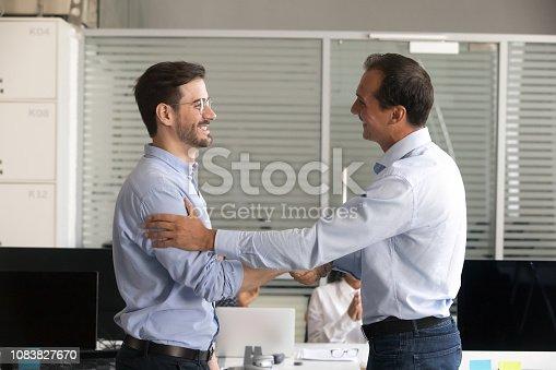 istock Friendly middle aged boss handshaking male employee 1083827670