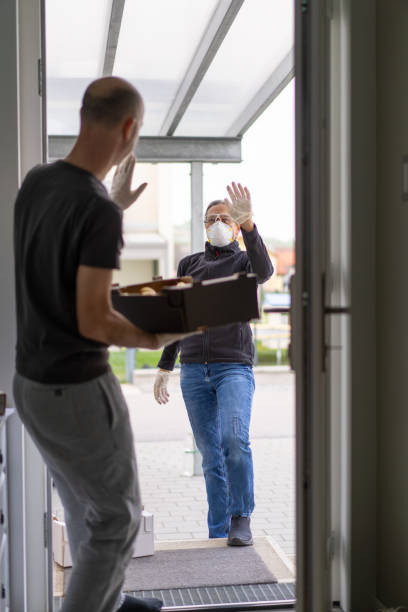 friendly neighborly help during hard times of coronavirus pandemic woman delivering food boxes with fresh fruits and vegetables at door steps of private house during coronavirus ciris curfew, man in open door quarantine, both waving friendly with enough social distance, view from inside the house flatten the curve stock pictures, royalty-free photos & images