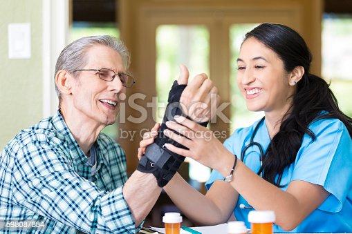 Beautiful Hispanic mid adult home health care nurse carefully examines Caucasian senior man's wrist. The man is wearing a brace on his injured wrist.