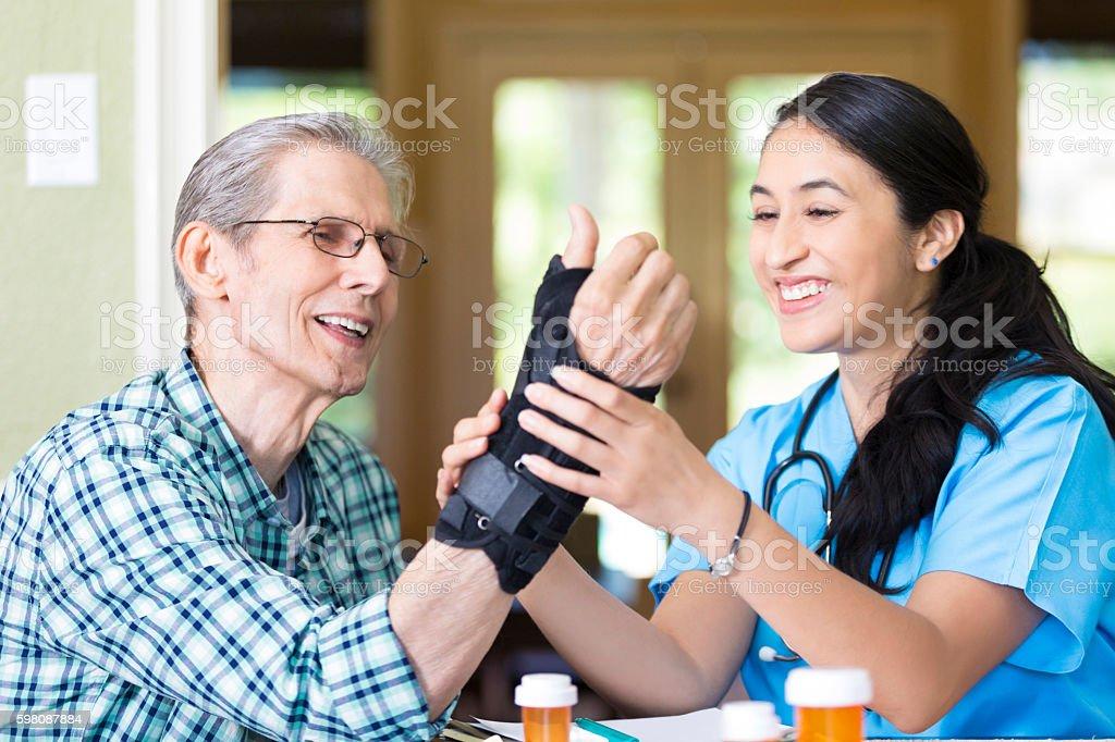 Friendly nurse examines senior patient's wrist stock photo