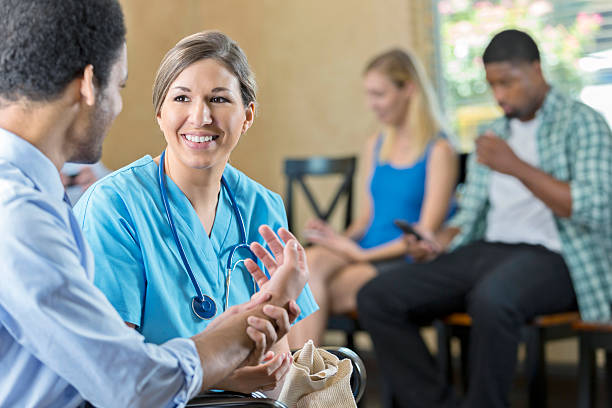 Friendly nurse examining patient in hospital triage center stock photo