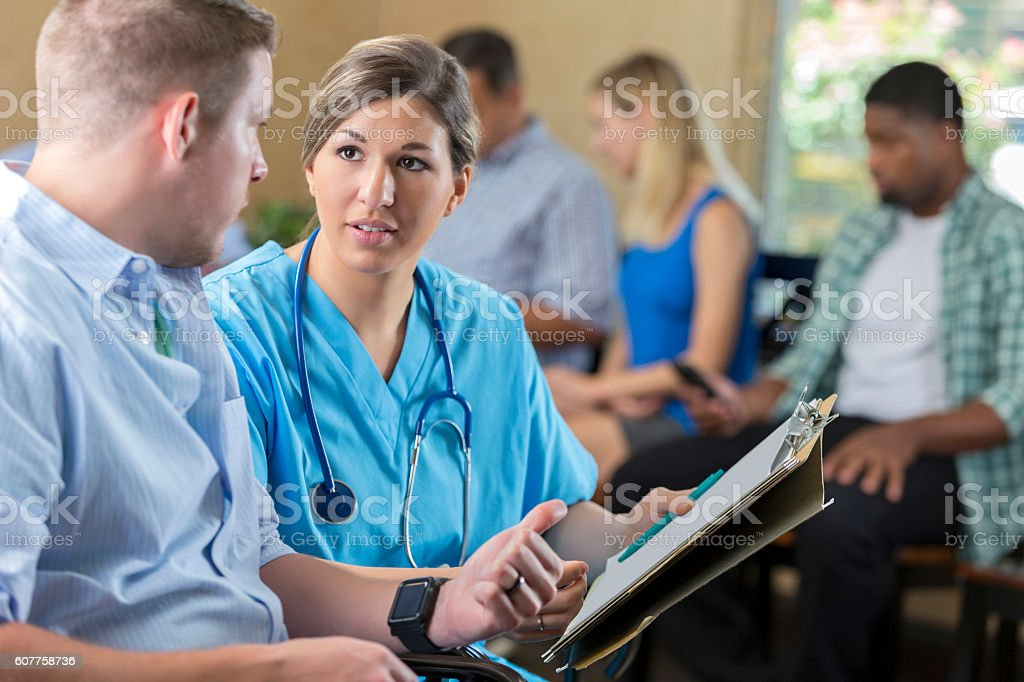 Friendly nurse examining patient in hospital triage center, stock photo