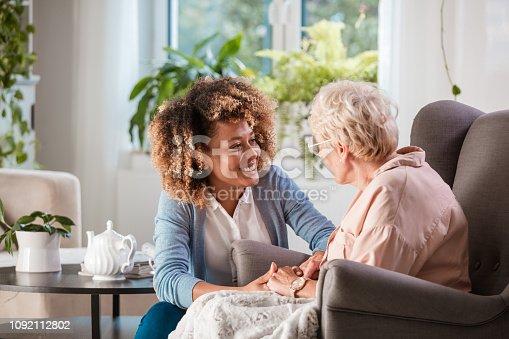 istock Friendly nurse supporting an eldery lady 1092112802