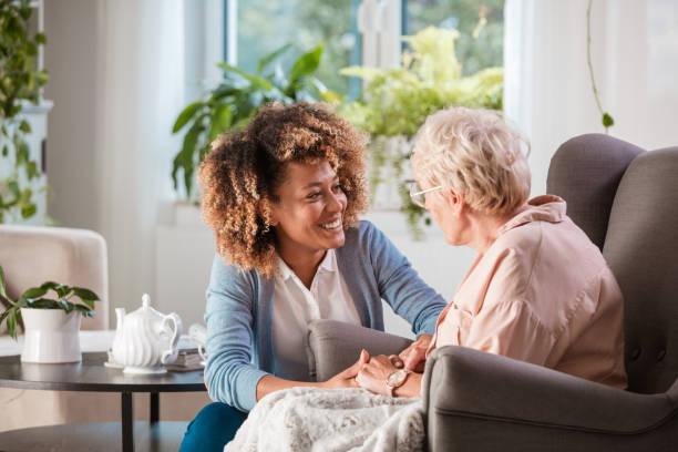 vänliga sjuksköterska stödja en äldre dam - omsorg bildbanksfoton och bilder