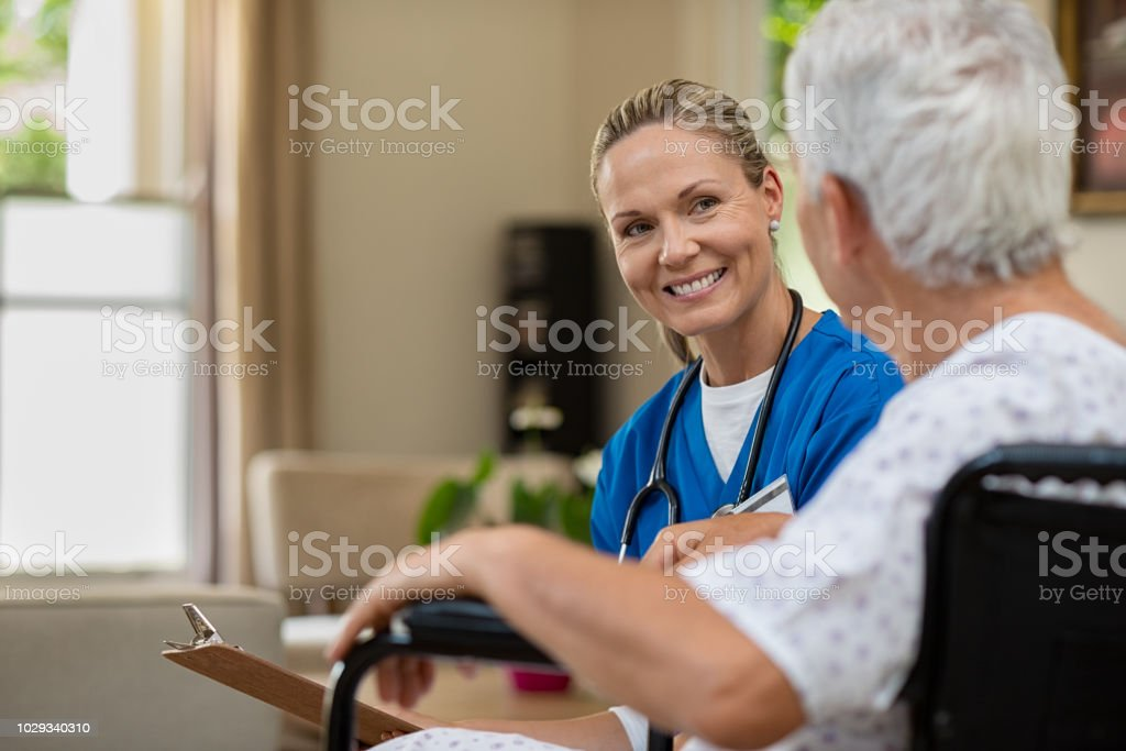 Enfermera amable hablando con el paciente mayor - foto de stock