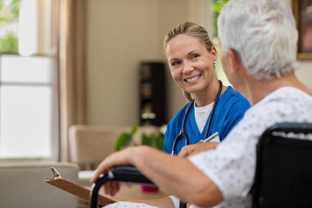 friendly nurse talking to senior patient - nurse stock pictures, royalty-free photos & images