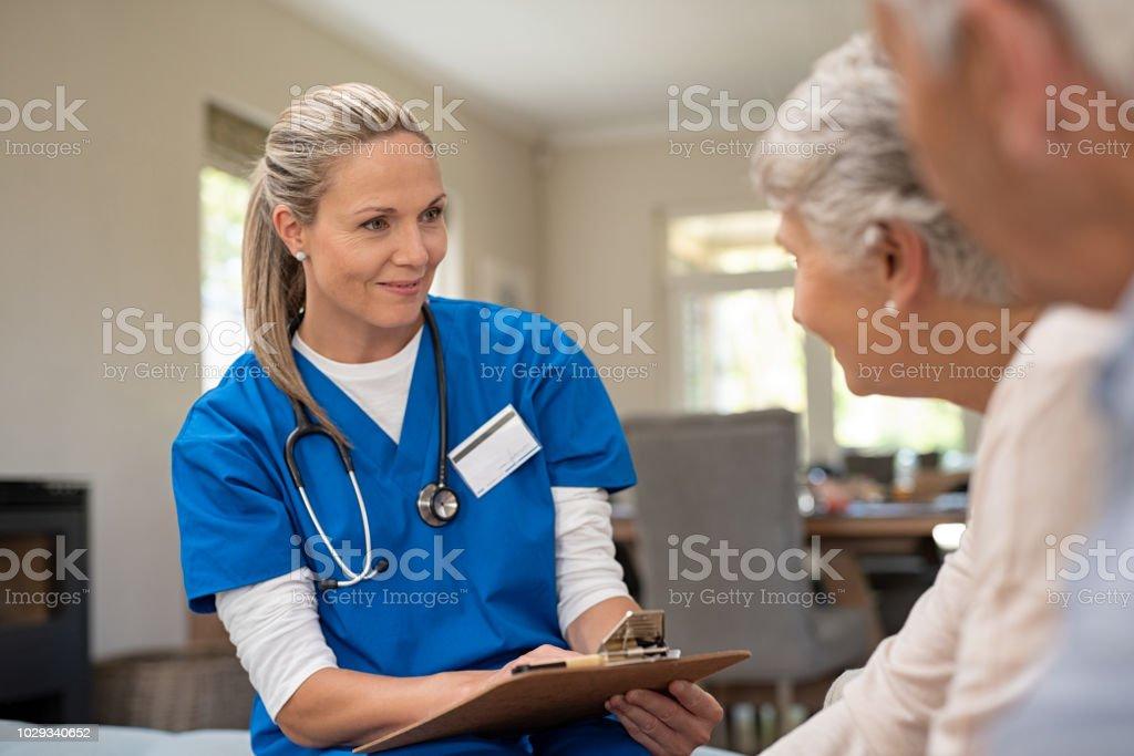 Freundliche Krankenschwester mit alten Ehepaar im Gespräch – Foto