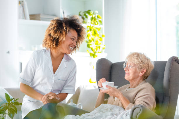 Friendly nurse with senior woman at home stock photo