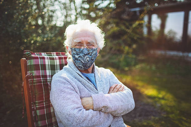 Friendly old senior wears a mask to protect against viruses and bacteria stock photo