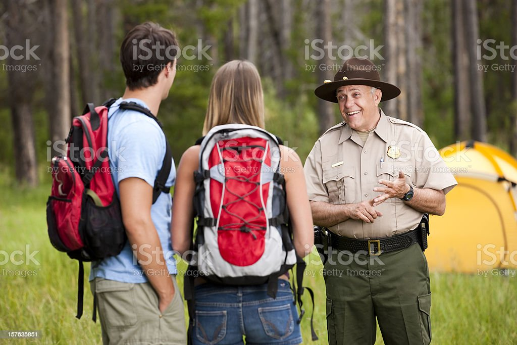 Friendly Park Ranger Helping Campers stock photo