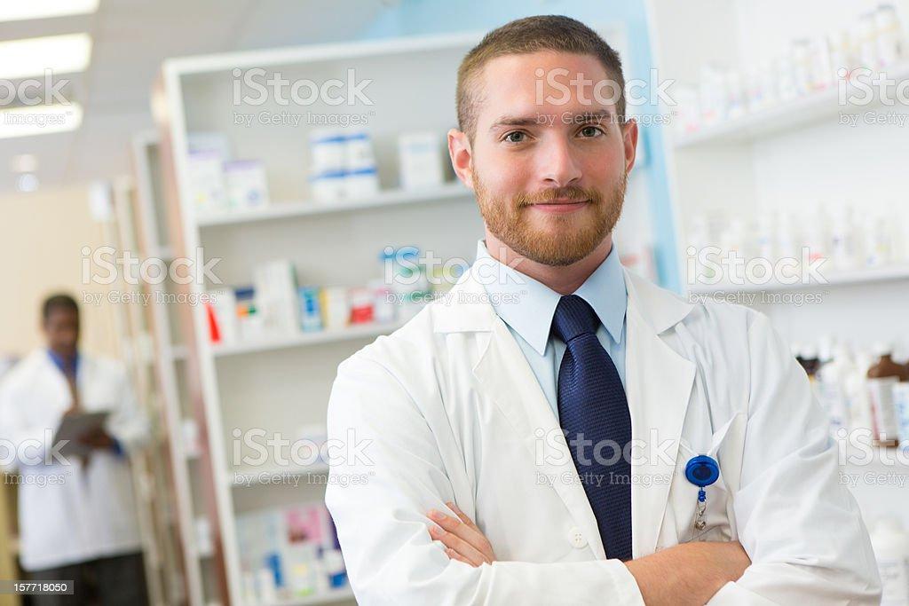 Friendly pharmacist at his pharmacy stock photo