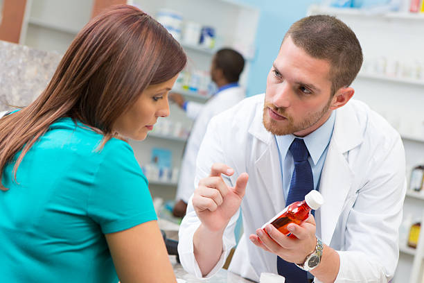 Friendly pharmacist explaining prescription medication dosage instructions to customer stock photo