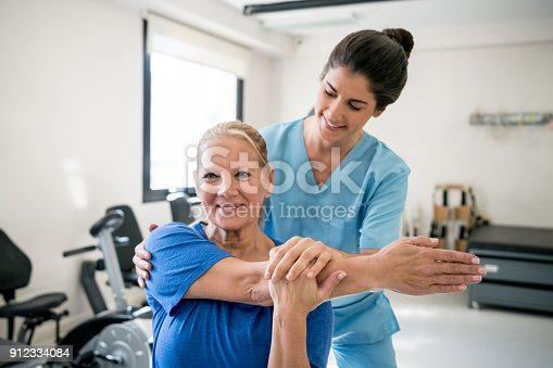 istock Friendly physical therapist holding senior patient while she stretches her shoulder 912334084