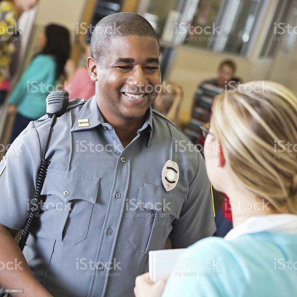 Friendly police officer talking with school teacher after safety demonstration stock photo
