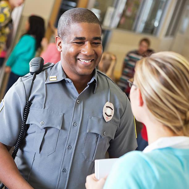 amichevole agente di polizia parlando con insegnante di scuola dopo la dimostrazione di sicurezza - talk in a radio foto e immagini stock