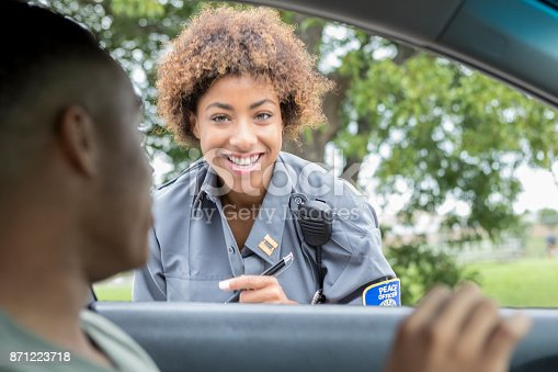 From the point of view of a front seat passenger, a smiling young female police officer crouches to speak to a stranded driver through an open car window.  She listens to his car trouble before radioing for help.