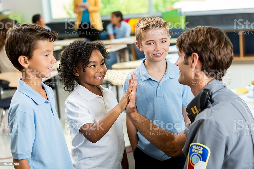 Friendly policeman gives high five to excited student stock photo