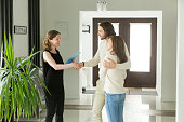 Friendly realtor and young couple shaking hands standing in hallway, real estate agent handshaking clients at meeting, showing selling buying property for rent sale, discussing deal with customers