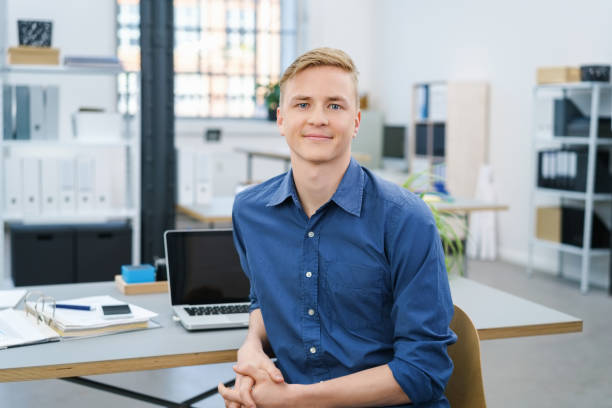 Friendly relaxed young businessman in the office Friendly relaxed young businessman in the office turning in his chair to look at the camera with a warm smile apprentice stock pictures, royalty-free photos & images