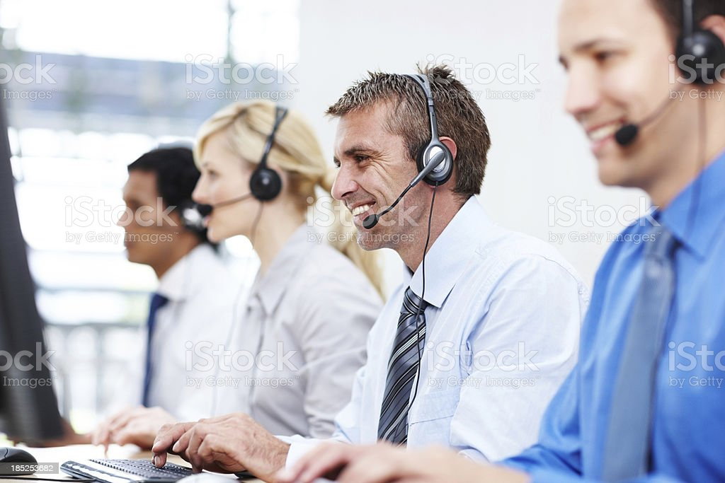 Friendly representatives with headsets in office royalty-free stock photo