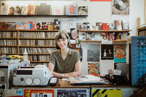 Portrait of a female retail worker standing behind the counter in a record store, smiling at camera.