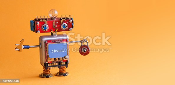 istock Friendly robot toy with key padlock on orange background. Cyborg smiley face, red head blue monitor body. digital message locked. copy space 842553746