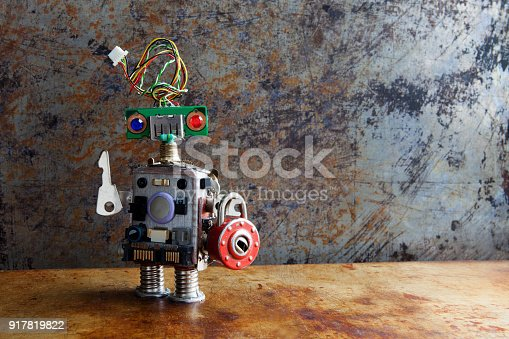 istock Friendly robot toy with key padlock on vintage background 917819822