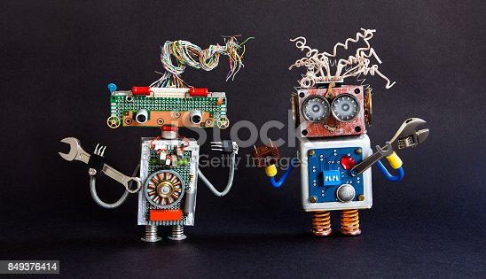 istock Friendly robots maintenance service concept. Creative design cyborg toys, adjustable spanner hand wrench on black background. Selective focus 849376414