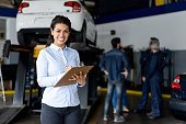 Friendly sales assistant at a car workshop holding a list on clipboard smiling at camera  - Incidental people at background