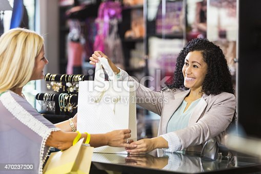 istock Friendly sales clerk with customer at checkout counter 470237200