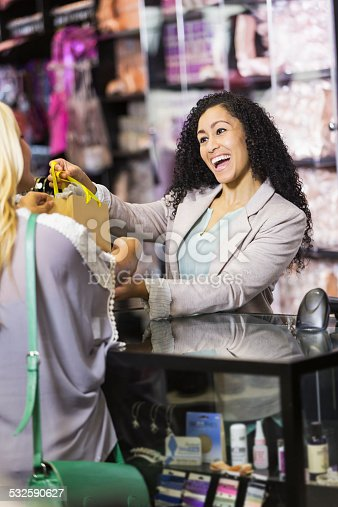 536272741istockphoto Friendly sales clerk with customer at checkout counter 532590627
