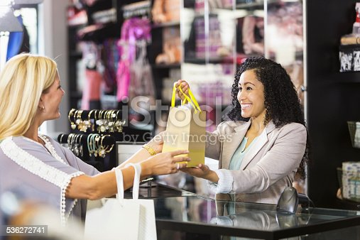 536272741istockphoto Friendly sales clerk with customer at checkout counter 536272741