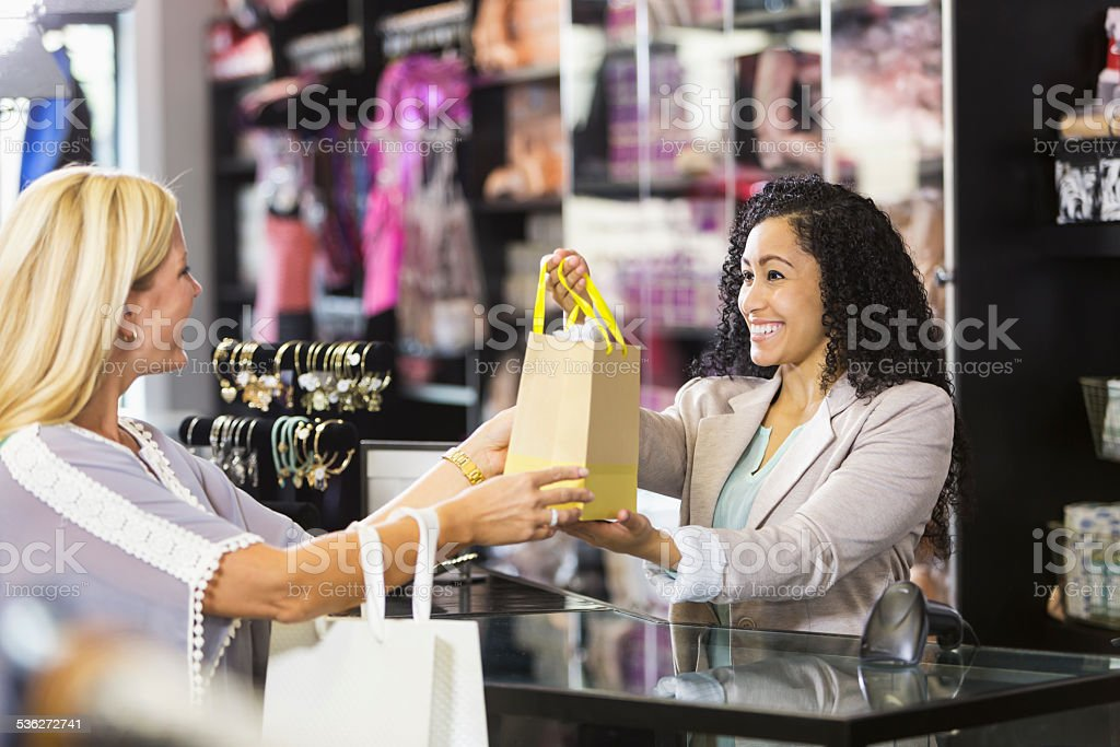 Friendly sales clerk with customer at checkout counter stock photo