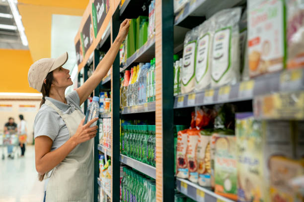 friendly sales woman reaching for a product on supermarket display - supermarket worker imagens e fotografias de stock
