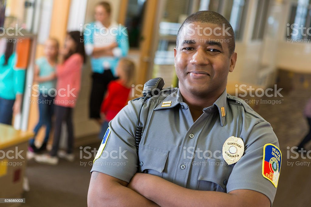 Friendly school security guard working on elementary school campus stock photo