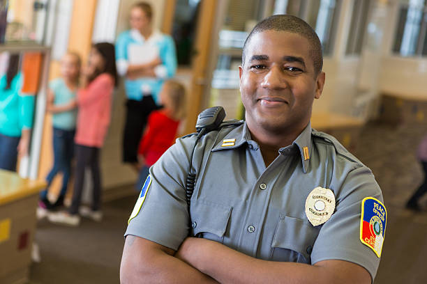 Friendly school security guard working on elementary school campus Friendly school security guard working on elementary school campus security staff stock pictures, royalty-free photos & images