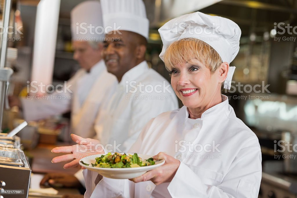 Friendly senior chef with completed dish in restaurant kitchen royalty-free stock photo