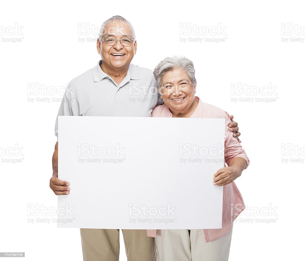 Friendly senior couple holding a sign stock photo