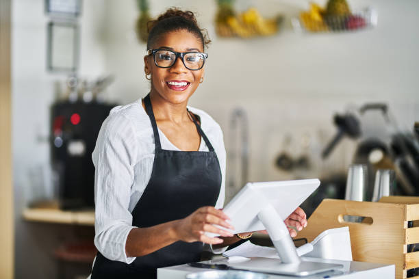 friendly shop assistant ready to take customer orders at register in restaurant stock photo