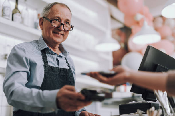 Friendly shop owner in glasses accepting payment from customer Waist up portrait of good-looking gentleman in apron holding terminal for contactless payment and smiling assistant stock pictures, royalty-free photos & images