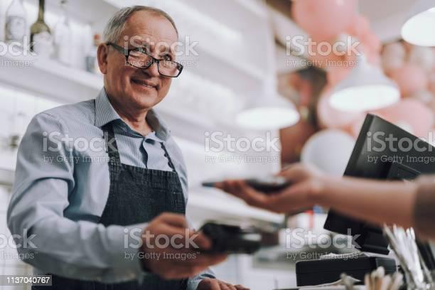 Friendly Shop Eigenaar In Glazen Accepteren Betaling Van Klant Stockfoto en meer beelden van Actieve ouderen