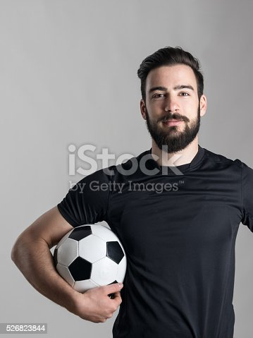 istock Friendly smiling bearded soccer player holding ball under his arm 526823844