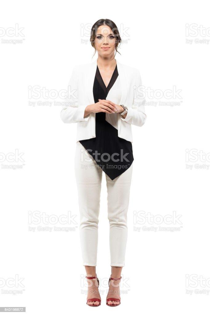 Agradable sonriente negocios mujer presentadora en traje formal con las manos cruzadas mirando a cámara foto de stock libre de derechos