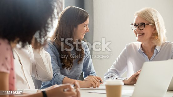 637940820 istock photo Friendly smiling old and young businesswomen talking laughing at meeting 1135346387