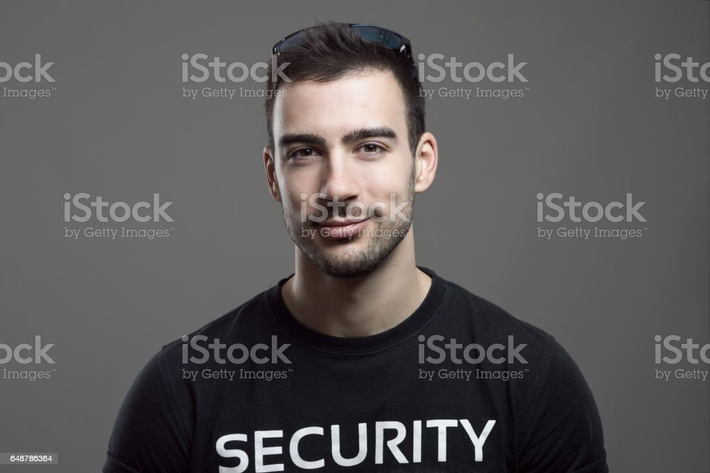 Friendly smiling security guard looking at camera stock photo