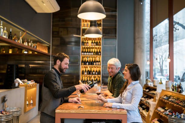 Friendly sommelier serving wine to a couple learning how to taste wine at a winery stock photo