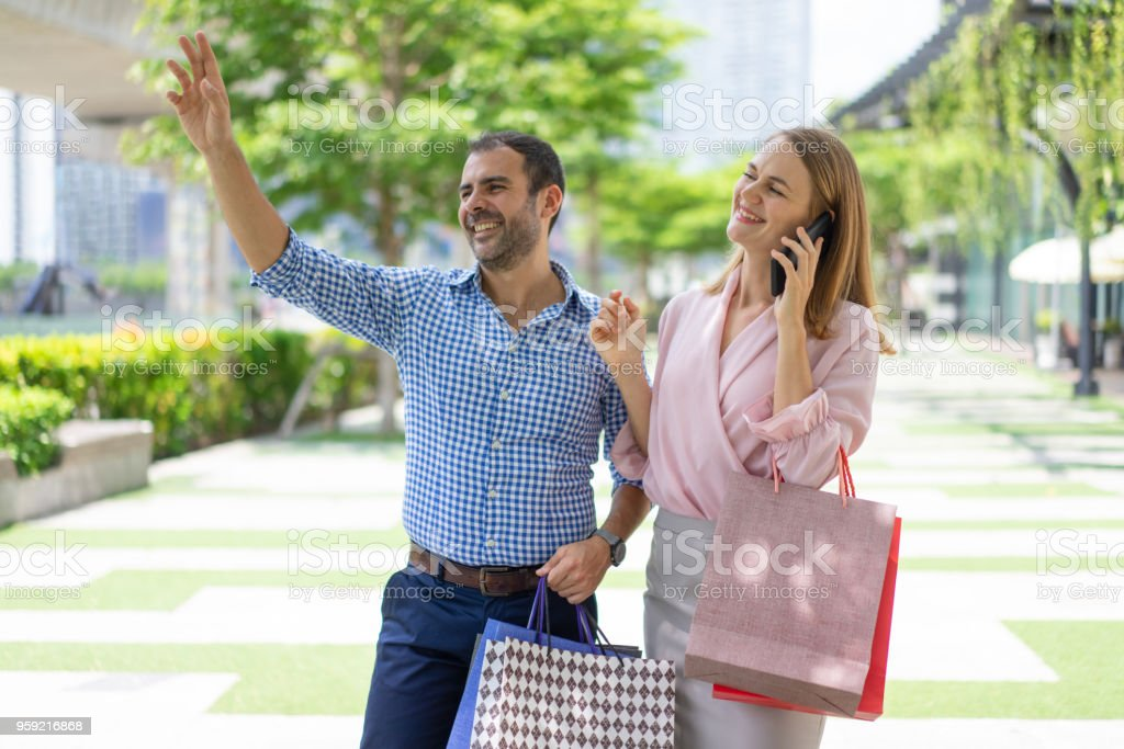 Friendly stylish couple of shoppers greeting someone on street stock friendly stylish couple of shoppers greeting someone on street royalty free stock photo m4hsunfo