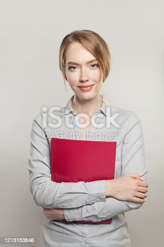 Friendly successful woman with documents standing against white background