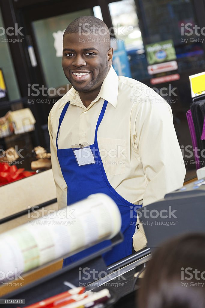Friendly supermarket cashier assisting customers at checkout royalty-free stock photo